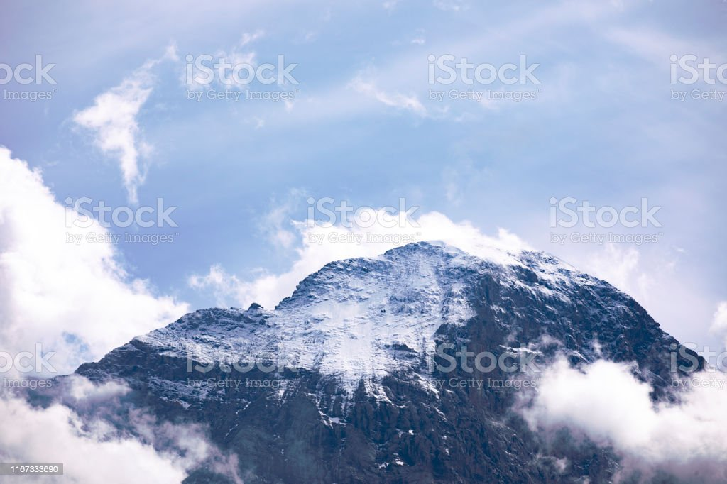 Solitude, alone peak of snowcapped mountain with surrounding clouds.