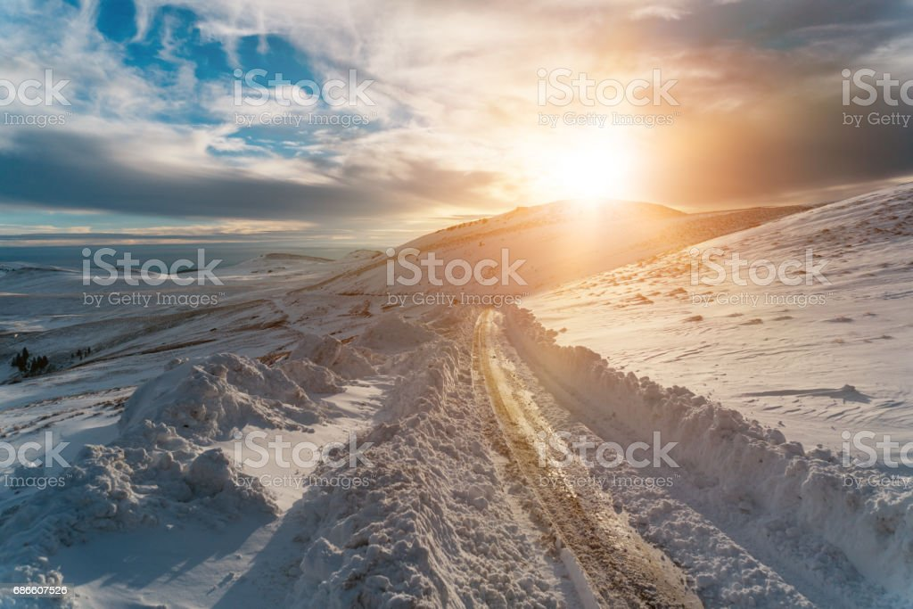 Snowy road and mountains in winter royalty-free stock photo