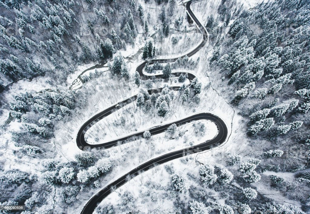 Snowy road in the forest. Extreme winding road high up in the mountains stock photo