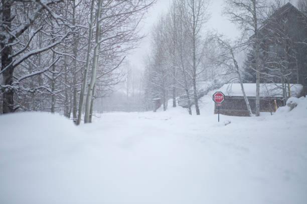 Snowy road in winter through village. stock photo