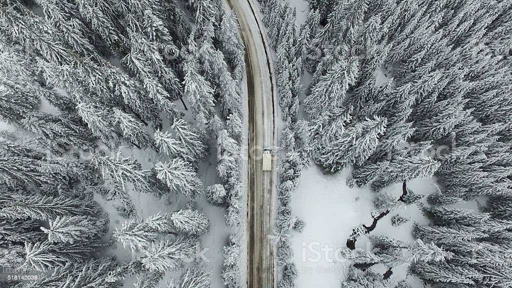 Snowy Road with a Car in the Forest stock photo