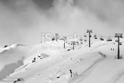 Snowy ski slope and ski-lift at ski resort at sunny winter evening. Caucasus Mountains, Shahdagh, Azerbaijan. Black and white toned landscape.