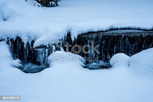 1141614053 istock photo snowy stream with a little waterfall frozen water closeup 994298070