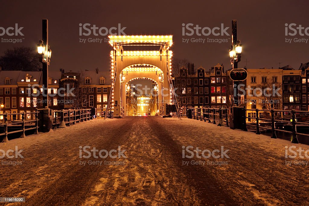 Snowy Thiny Bridge in Amsterdam the Netherlands at night stock photo