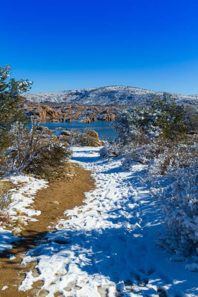 A snowy trail through the desert leading to Watson Lake stock photo