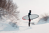 istock Snowy winter and surfer with surfboard. Winter beach and surfer in wetsuit. 1281769494