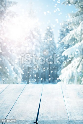 Winter background with snow-covered pine trees behind empty wooden planks