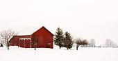 Winter snow scene with a rustic red barn covered with snow.