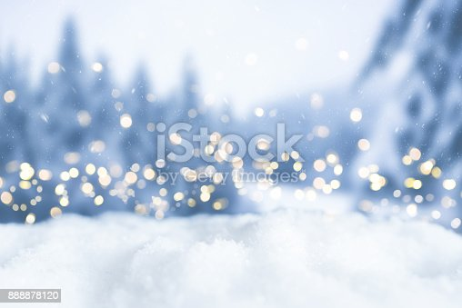 istock snowy winter christmas bokeh background with circular lights and trees 888878120