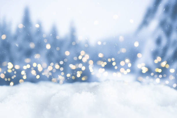 snowy winter christmas bokeh background with circular lights and trees stock photo