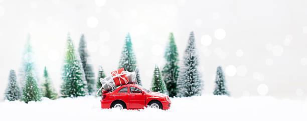 snowy winter forest with  red car carrying christmas presents - gutschein weihnachten stock-fotos und bilder