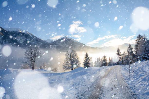 Paisagem de inverno nevado nos Alpes tiroleses com estrada gelada durante a queda de neve, Áustria Europa - foto de acervo