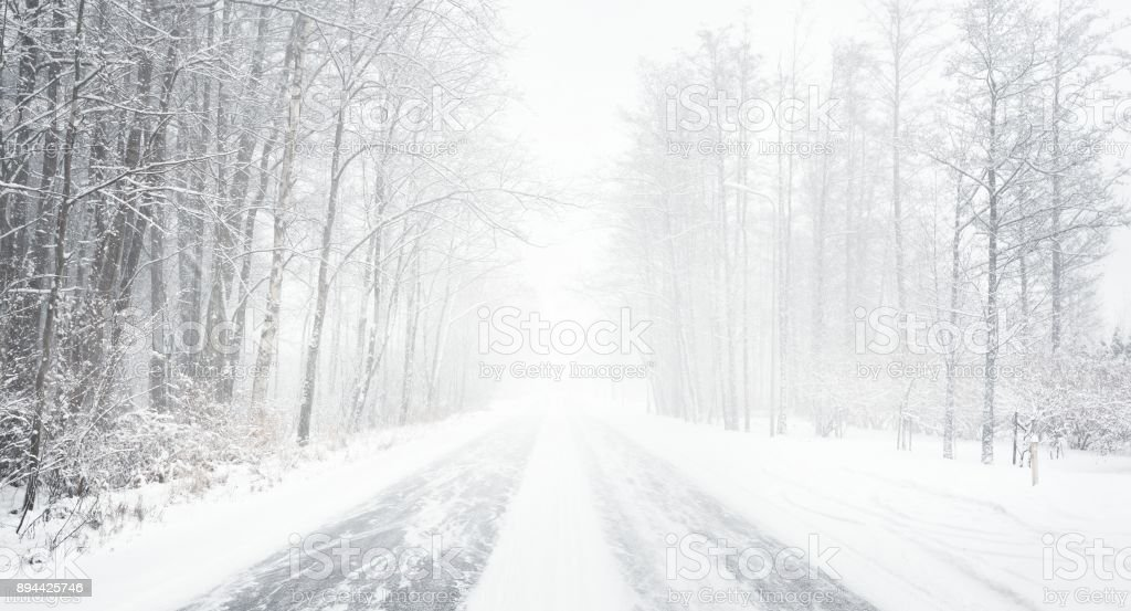 Snowy winter road during blizzard in Latvia stock photo