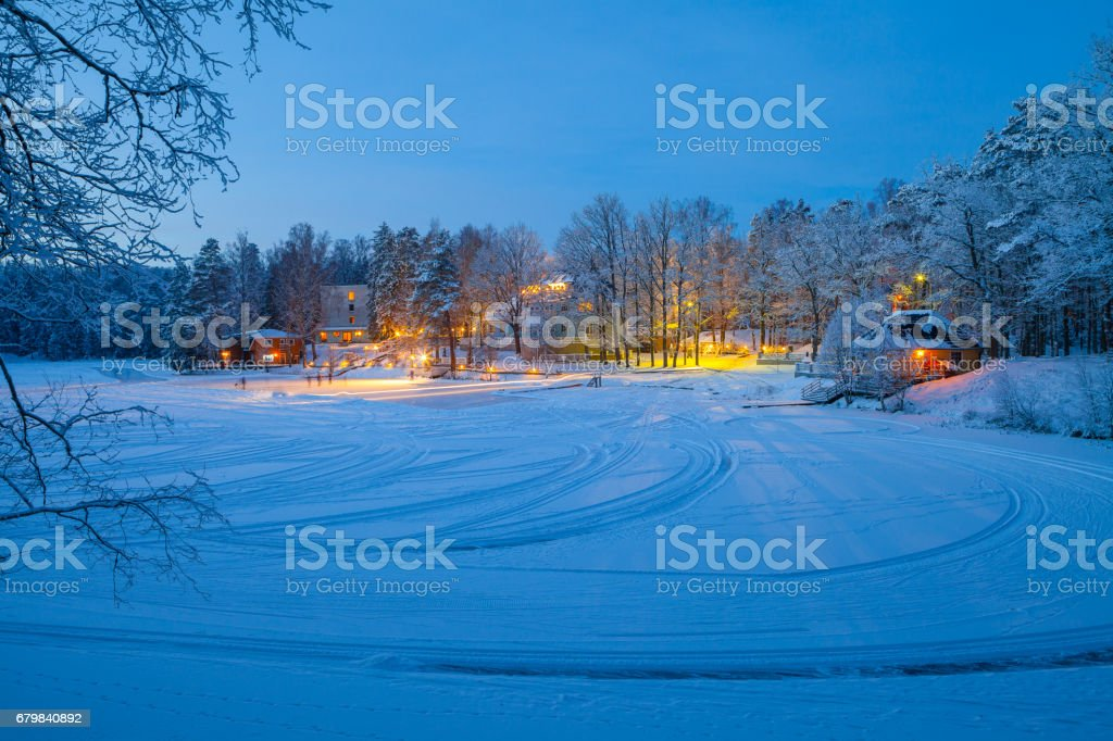 Snowy winter scene of illuminaned cottages in foresr near frozen lake stock photo