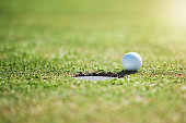 Closeup shot of a golf ball on the edge of a hole outside on a golf course during the day