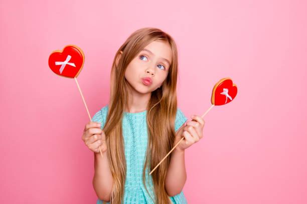 so nett, schön und lustig! porträt von schönen süßen mädchen leicht blauen kleid, sie süßigkeiten und gebäck, träumt von isoliert auf hellen rosa hintergrund - lutscher cookies stock-fotos und bilder
