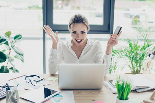 istock So easy! Excited business lady in formal wear is doing online shopping in internet. She is relaxing and buying goods easily, nice wrk place, windows behind her, green plants 928771346