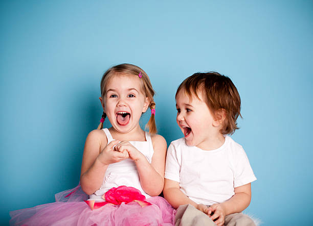 so funny! girl and boy laughing hysterically - sister stock photos and pictures