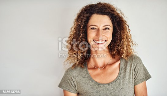 Portrait of a happy and confident young woman standing posing against a gray wall