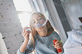 Cute little girl blowing a soap bubble while spending time at home