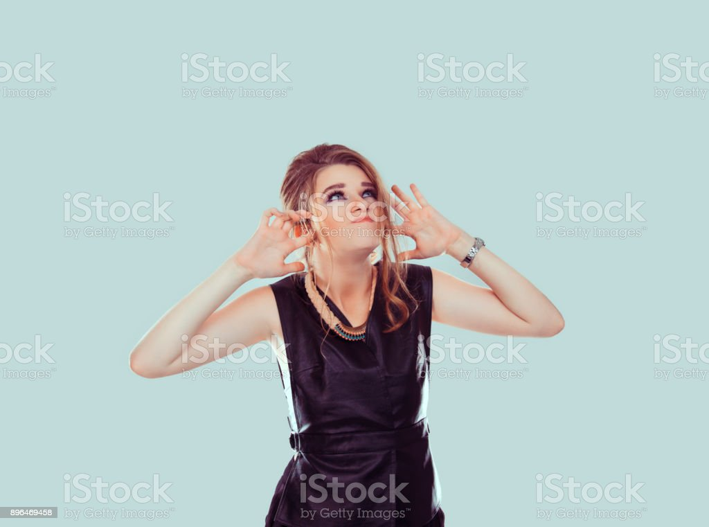 So loud. angry unhappy stressed woman covering her ears looking up stop making loud noise it's giving me headache isolated light on green wall background. Negative emotion face expression feeling stock photo