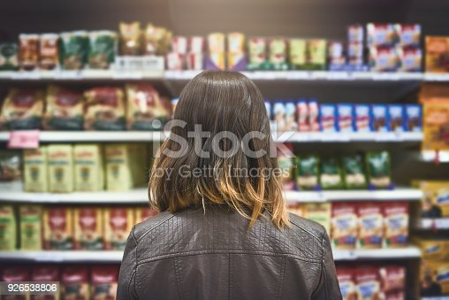Rearview shot of a young woman shopping at a grocery store