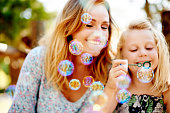 Shot of a happy young mother and daughter blowing bubbles in the park