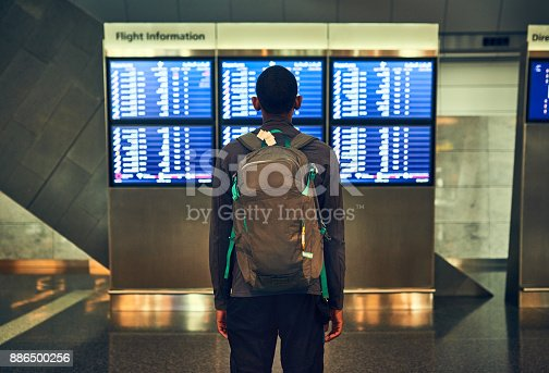 Shot of a man checking the flight times in an airport