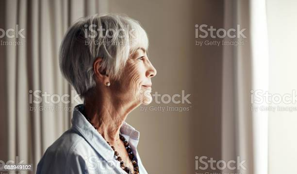 Cropped shot of a senior woman looking out the window at home