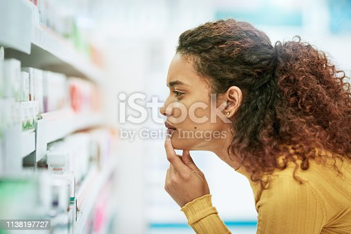Shot of a young woman browsing the shelves of a pharmacy