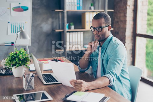 istock So nerd and focused. Young handsome afro student is concentrated on studying. He is in a casual outfit with project at his work station 929115746