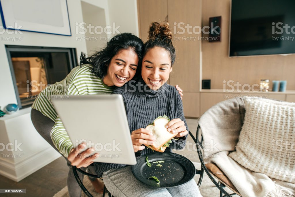 Two female students in a living room with tablet