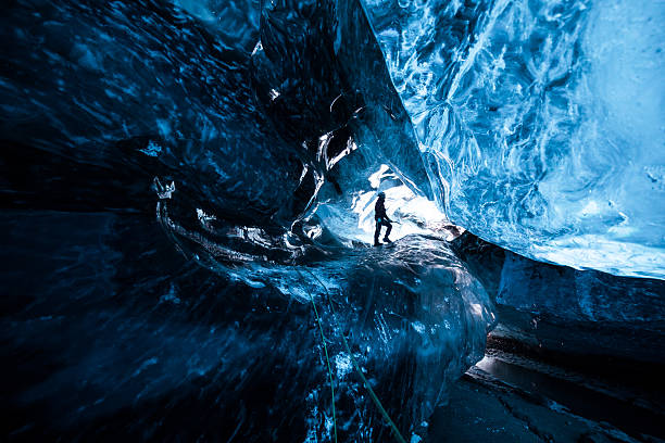 So small Inside an icecave in Vatnajokull, Iceland. A climber silhoutted against the ice. The ice is thousands of years old and so packed it is harder than steel and crystal clear. These caves are formed by meltwater that rushes from over and underneath the glacier and creates these wonderful sights jokulsarlon stock pictures, royalty-free photos & images