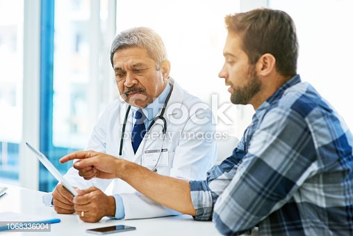 Shot of a confident mature male doctor consulting with a patient inside of his office during the day