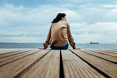 Back shot of a woman sitting on the edge of a seaside boardwalk