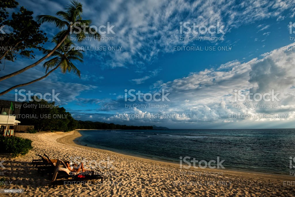 Soaking on a soft afternoon light in Seychelles, a tourist is relaxing on a golden beach. stock photo