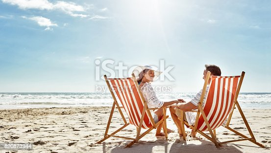 Shot of a mature couple relaxing together on deck chairs at the beach
