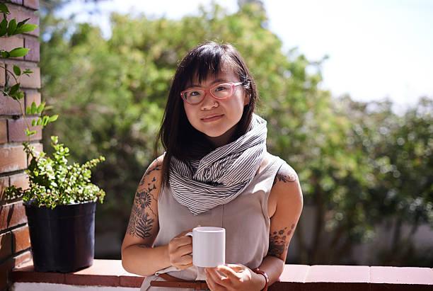 soaking up some sunshine while enjoying her coffee - kaffeetasse tattoo stock-fotos und bilder