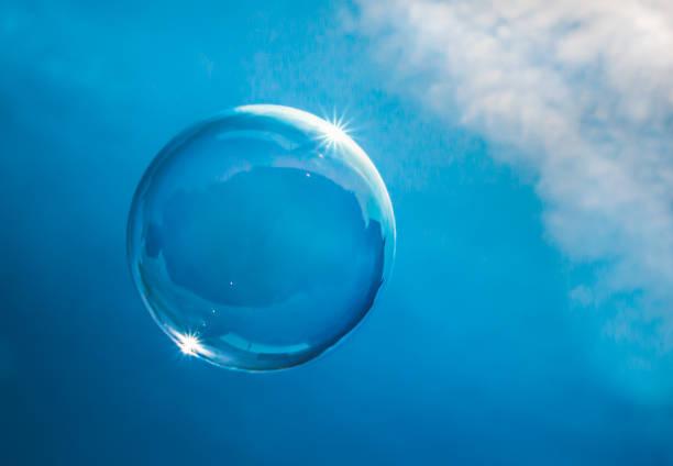 Seifenblase, die in einem blauen Himmel schwimmt, mit Wolken, die das Sonnenlicht an seinem Rand fangen. Zerbrechliches Erd-oder Blauplanetenkonzept – Foto