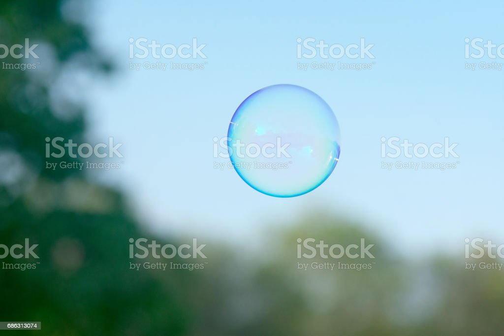 A soap bubble lifts off from the backyard. stock photo