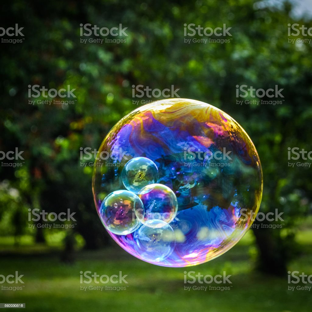 soap bubble with smaller bubbles inside close up stock photo