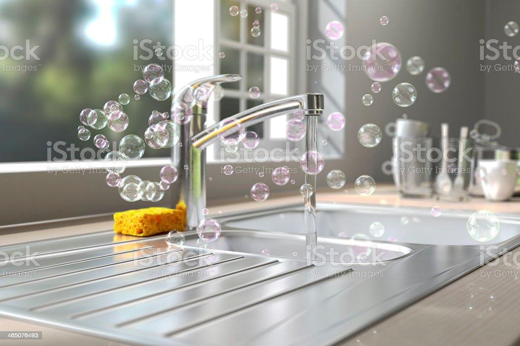 Soap bubbles floating around kitchen sink while washing dish stock photo