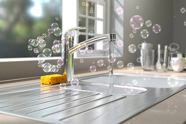 soap bubbles floating around kitchen sink while washing dish - kitchen sink stock photos and pictures