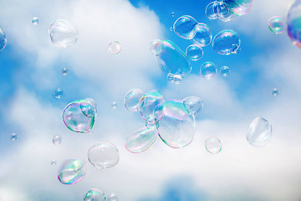 Soap bubbles floating in cloudy blue sky stock photo