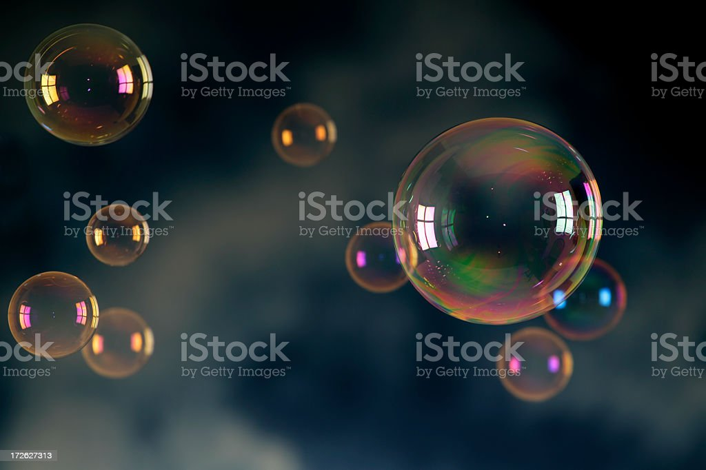Soap bubbles floating in front of a dark background royalty-free stock photo