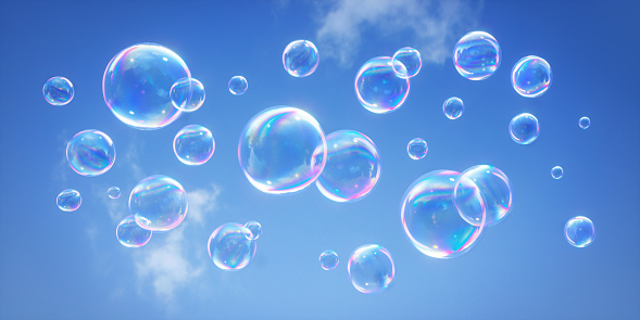 Lots of soap bubbles flying through the air with clear blue sky background