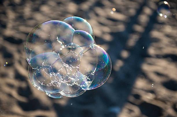soap bubbles on beach - riesen seifenblasen zauberstäbe stock-fotos und bilder