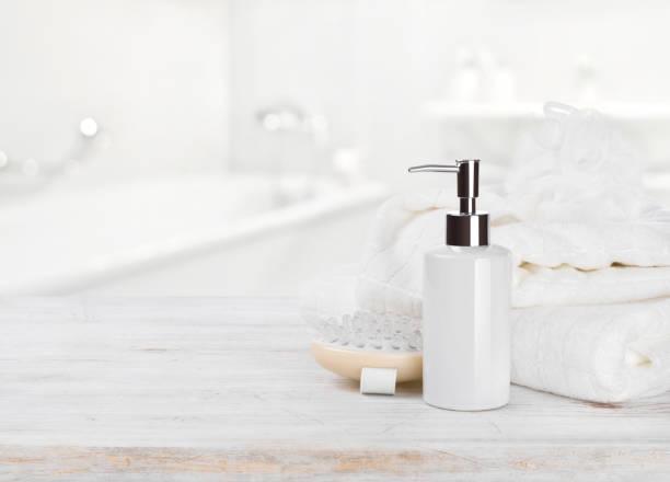 soap dispencer, towels, massager and wisp of bast over blur - prodotto per l'igiene personale foto e immagini stock