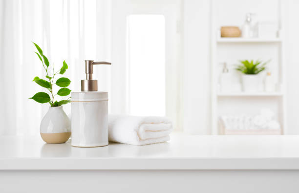 Soap dispenser and spa towel on pastel bathroom window interior stock photo
