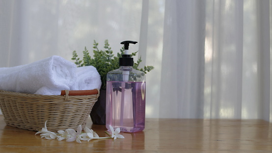 Soap dispenser and spa towel ,Roll up of white towels on white table with copy space